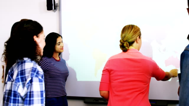 Teacher and students discussing over world map on whiteboard in classroom video