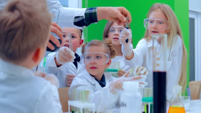 Teacher and students doing science experiment in school classroom. Children in chemistry class video