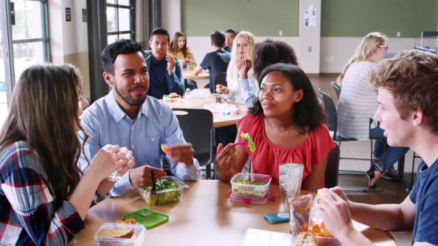 nauczyciel i uczniowie jedzący lunch w stołówce w szkole średniej podczas przerwy - stołówka filmów i materiałów b-roll