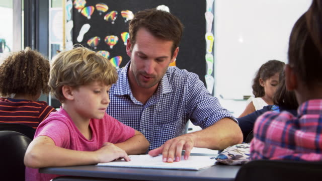 Teacher and young schoolboy looking at notebook in class video