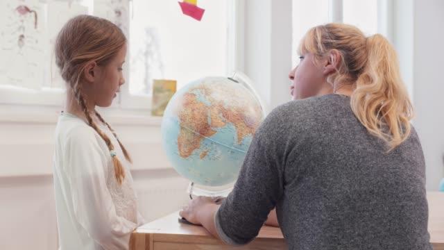 läraren ber sin elev att hitta något på globen i klass rummet - bordsjordglob bildbanksvideor och videomaterial från bakom kulisserna