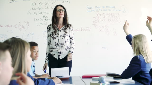 Teacher Asking Pupils Questions A teacher in a classroom is asking her pupils questions about the subject in lesson. faq stock videos & royalty-free footage