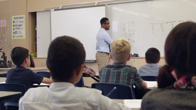 vídeos y material grabado en eventos de stock de profesor pide pregunta en clase de matemáticas, atrás punto de vista, toma en r3d - clase de escritura