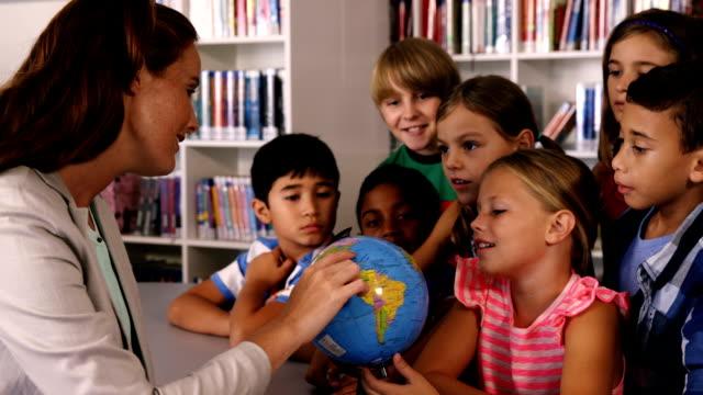 Teacher assisting school kids in reading globe in library video