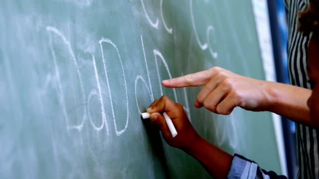 Teacher assisting schoolboy in writing alphabet on chalkboard - video