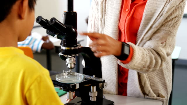 Teacher assisting schoolboy with microscope in classroom video