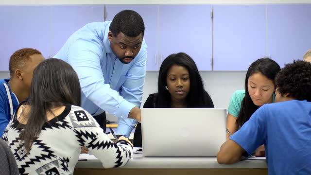 Teacher Assists Multi-Ethnic Students Using Computer video