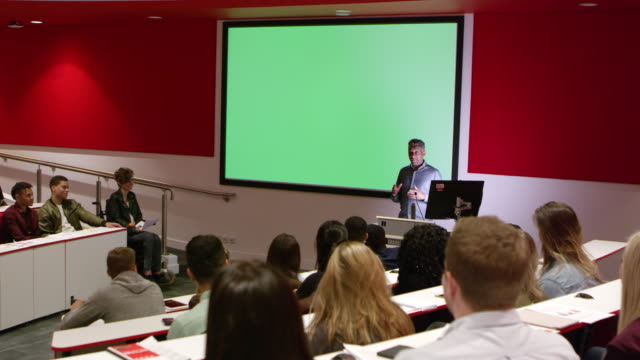 Teacher at lectern in lecture theatre presenting to students, shot on R3D video