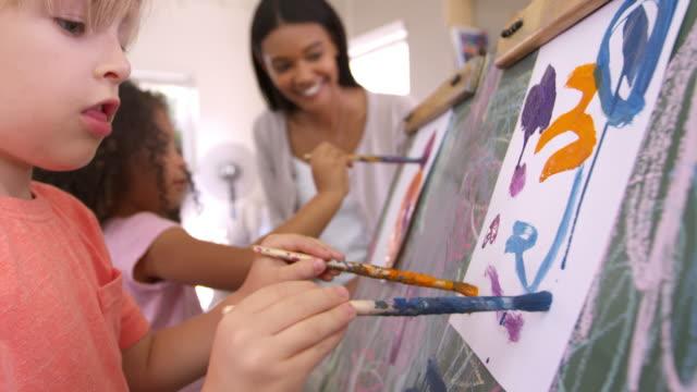 Teacher At Montessori School Helping Children in Art Class