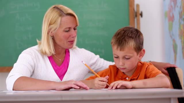 Teacher at school helps student in classroom video