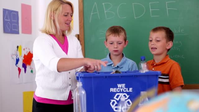 Maestro en la escuela enseña a los estudiantes sobre reciclado - vídeo