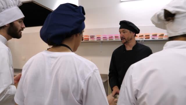 stockvideo's en b-roll-footage met leraar chef-kok onderwijzen zijn studenten over verschillende ingredientes en vervolgens een knoflook die een student hem geeft ruiken - dranken en maaltijden