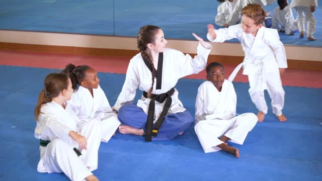 vidéos et rushes de enseignant, enfants dans la classe de taekwondo, s'asseoir sur l'étage - arts martiaux
