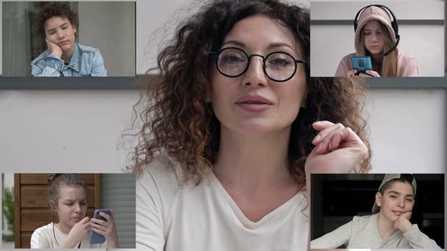 教師は生徒のグループのためにビデオレッスンを行います。学生は明らかに退屈で、誰もが自分のビジネスで忙しいです。遠隔学習の問題 - 人里離れた点の映像素材/bロール