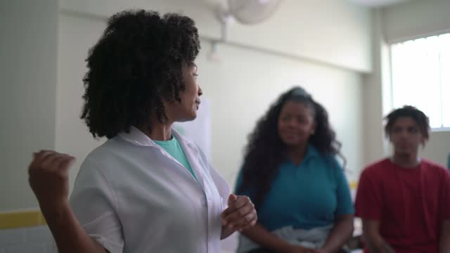 Teacher doing an informal seminar to students at school