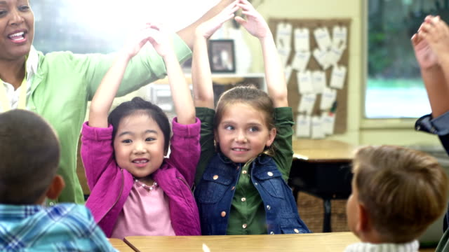 Teacher, elementary students in classroom, waving hands