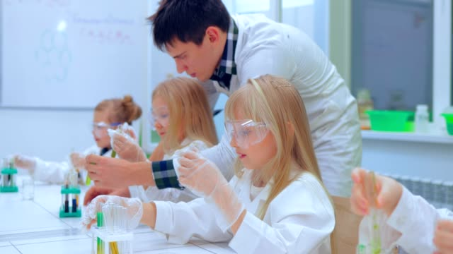 Teacher explaining an experiment to a high school chemistry class together. Teacher teaching group of students in school science class video