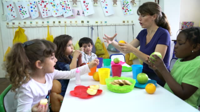 Teacher explaining fruits to students in classroom Mature teacher explaining preschool students about fruits. Woman is sitting with kids at desk during lunch. They are at classroom in school building. elementary age stock videos & royalty-free footage