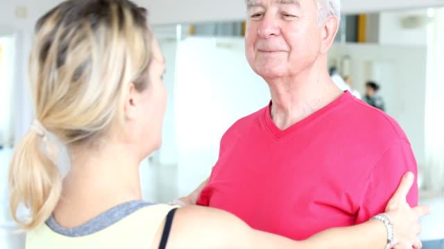 Teacher explaining shoulder exercise to senior man video