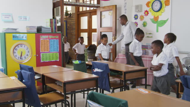Profesor saluda a los niños llegar al aula de la escuela primaria - vídeo
