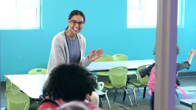 Profesor saluda al entrar en el aula de preescolar - vídeo