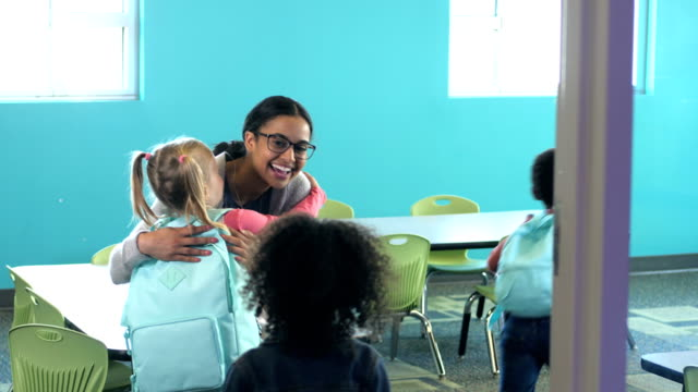 teacher greets preschoolers entering classroom - teacher stock videos & royalty-free footage