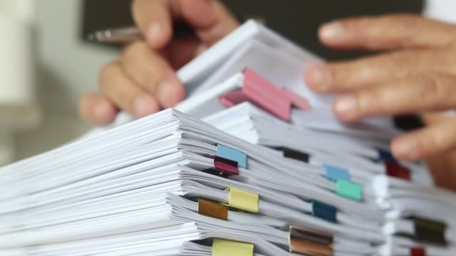 teacher hands is searching for student's homework assignments archive with colorful papers on table to make a check and inspect. stack of paperwork and reports. education and business concept. - rapporto video stock e b–roll