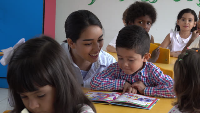 Teacher helping a student read a book while laughing