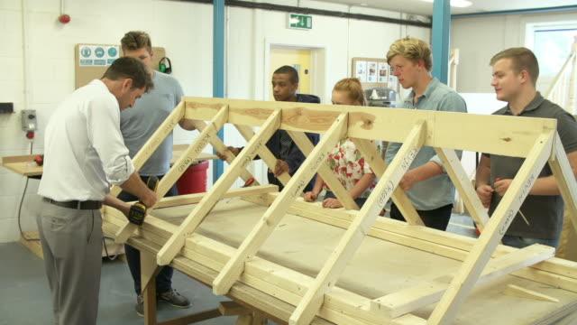учитель, помогая студентам учиться плотницкие работы - class стоковые видео и кадры b-roll