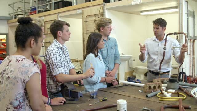 учитель, помогая студентам учиться сантехнические - class стоковые видео и кадры b-roll