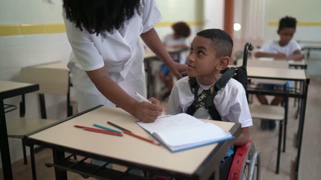 Teacher helping disabily student in the classroom video