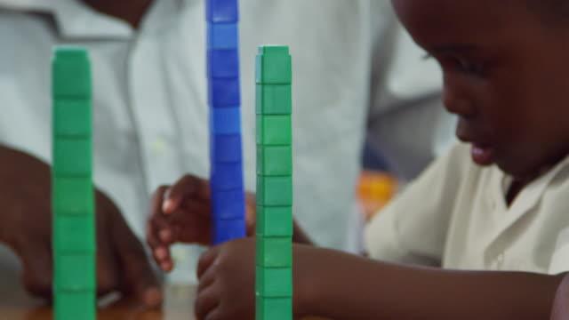 Teacher helping elementary school boy balancing blocks video