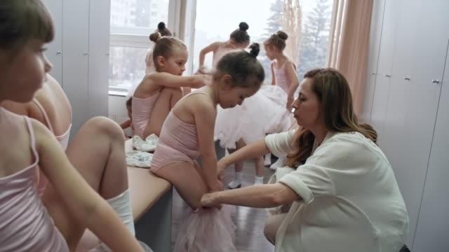 vídeos de stock e filmes b-roll de teacher helping girls with ballet clothes - tule têxtil