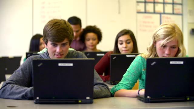 учитель помогает учащихся старших классов средней школы в классе с помощью ноутбуков - class стоковые видео и кадры b-roll
