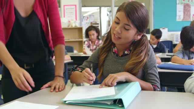 Teacher helping Hispanic schoolgirl at her desk, shot on R3D video