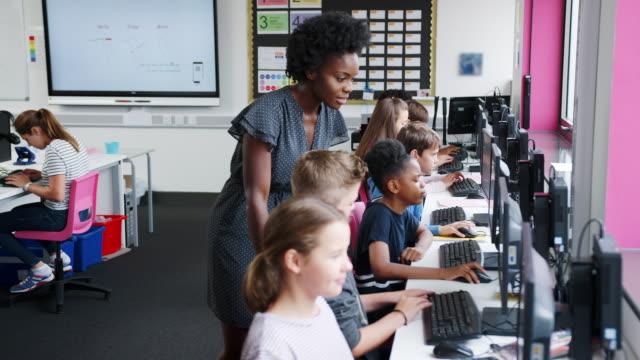 lehrer helfen männliche schüler in der linie der schülerinnen und schüler arbeiten an bildschirmen in computer-klasse - highschool lehrer stock-videos und b-roll-filmmaterial