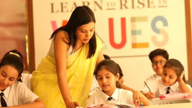 vídeos de stock e filmes b-roll de teacher helping schoolgirl with writing - cultura indiana