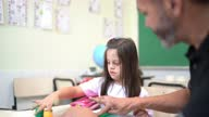 istock Teacher helping special needs student during arts class 1284102061