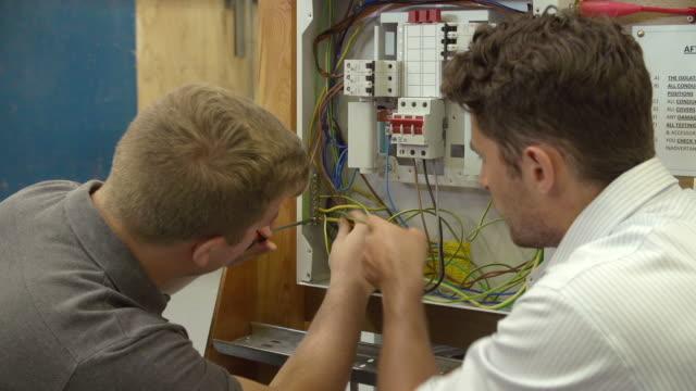 Profesor ayudando a estudiantes formación de electricista - vídeo
