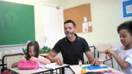 istock Teacher helping students during class activity 1284097946