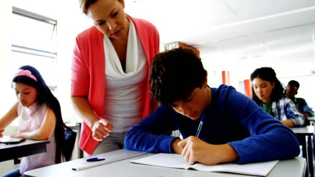 vídeos y material grabado en eventos de stock de profesor ayudar a los estudiantes con su trabajo en clase - clase de matemática