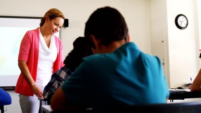 lehrer, die unterstützung der schüler bei den hausaufgaben im klassenzimmer - highschool lehrer stock-videos und b-roll-filmmaterial