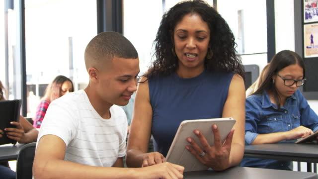 Teacher helping teenage schoolboy use tablet computer video