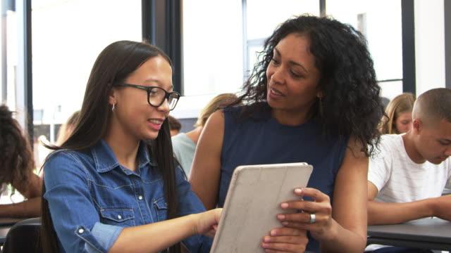 lehrer helfen teenager schulmädchen mit tablet-computer - grundschullehrer stock-videos und b-roll-filmmaterial