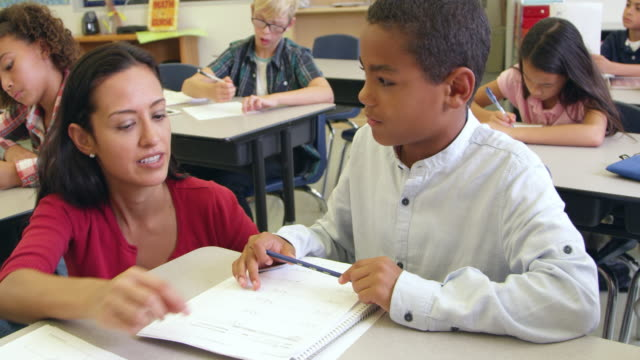 Teacher helps schoolboy in class, close up, shot on R3D video