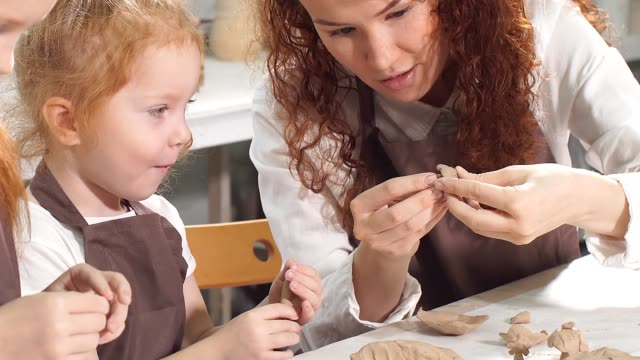 vídeos de stock e filmes b-roll de teacher helps the kid to cut out a clay figurine with spatula or knife, shows and explanes - teacher school solo