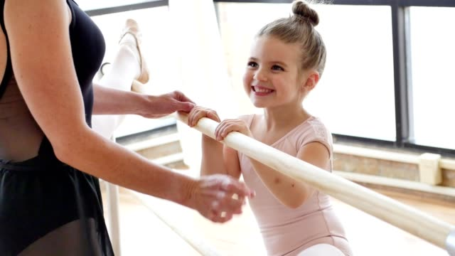 Teacher helps young ballerina while using ballet barre Unrecognizable ballet teacher shows an adorable preschool age ballerina how to use a ballet barre. The teacher's leg is up on the bar. The young ballerina smiles while trying to put her leg on the barre. leotard stock videos & royalty-free footage