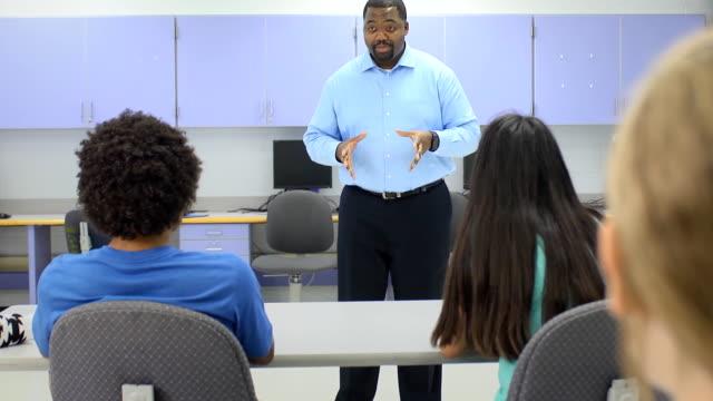 lehrer interaktion mit gruppe von studenten - highschool lehrer stock-videos und b-roll-filmmaterial