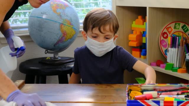 老師正在學前學校對4歲的男孩課桌進行消毒 - back to school 個影片檔及 b 捲影像