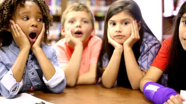 lehrer, bibliothekar liest buch für grundschüler in bibliothek oder im klassenzimmer. - storytelling videos stock-videos und b-roll-filmmaterial